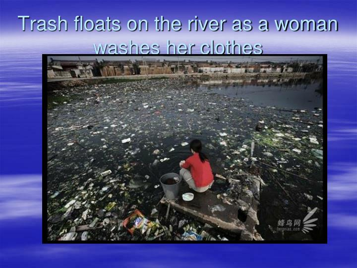 Trash floats on the river as a woman washes her clothes