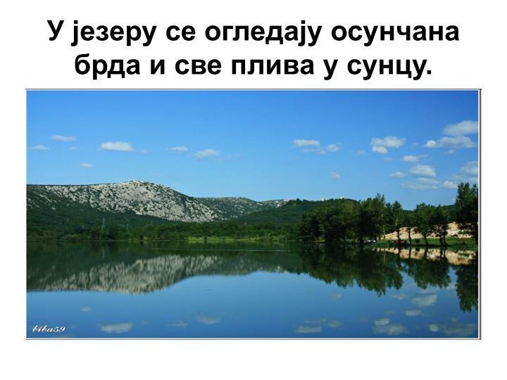 У језеру се огледају осунчана брда и све плива у сунцу.