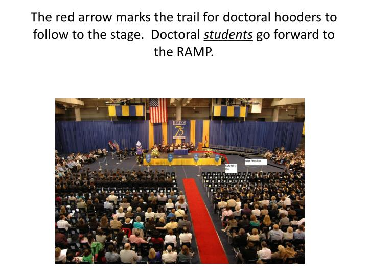 The red arrow marks the trail for doctoral hooders to follow to the stage.  Doctoral