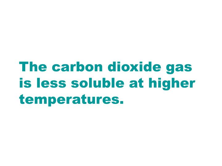 The carbon dioxide gas is less soluble at higher temperatures.