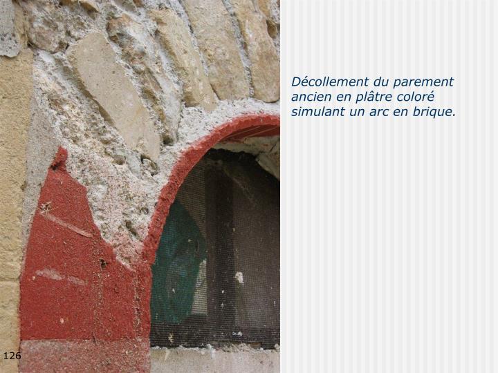 Décollement du parement ancien en plâtre coloré simulant un arc en brique.