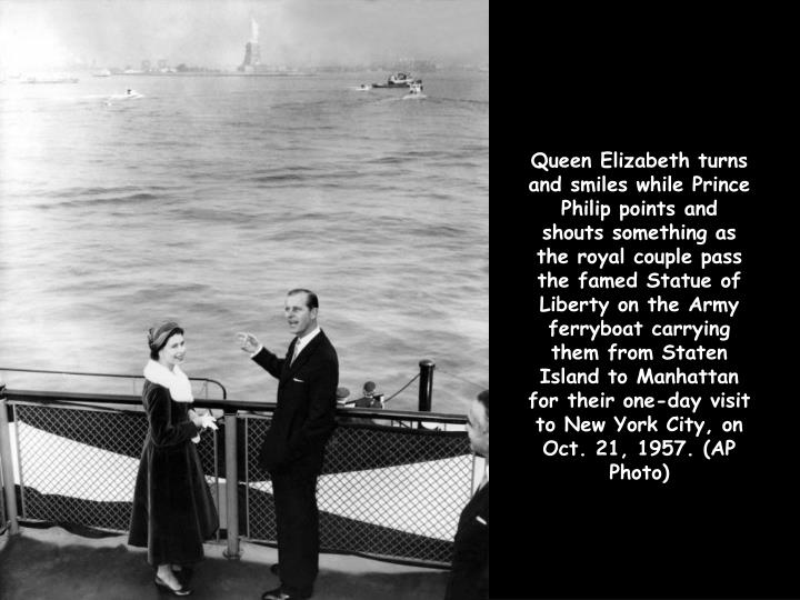 Queen Elizabeth turns and smiles while Prince Philip points and shouts something as the royal couple pass the famed Statue of Liberty on the Army ferryboat carrying them from Staten Island to Manhattan for their one-day visit to New York City, on Oct. 21, 1957. (AP Photo)
