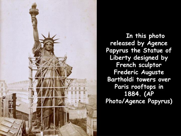 In this photo released by Agence Papyrus the Statue of Liberty designed by French sculptor Frederic Auguste Bartholdi towers over Paris rooftops in 1884. (AP Photo/Agence Papyrus)
