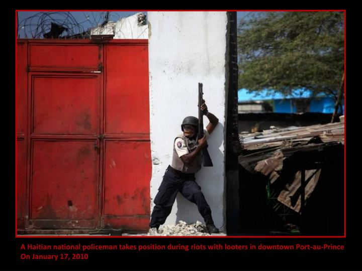 A Haitian national policeman takes position during riots with looters in downtown Port-au-Prince