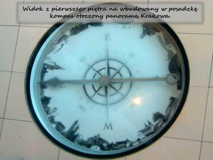 Widok z pierwszego pitra na wbudowany w posadzk kompas otoczony panoram Krakowa.
