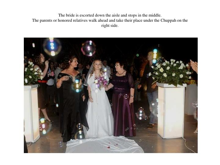 The bride is escorted down the aisle and stops in the middle.
