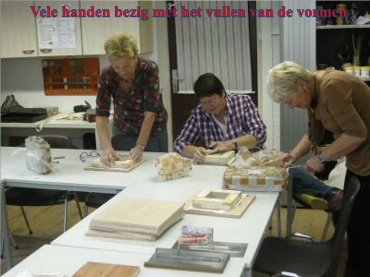 Vele handen bezig met het vullen van de vormen