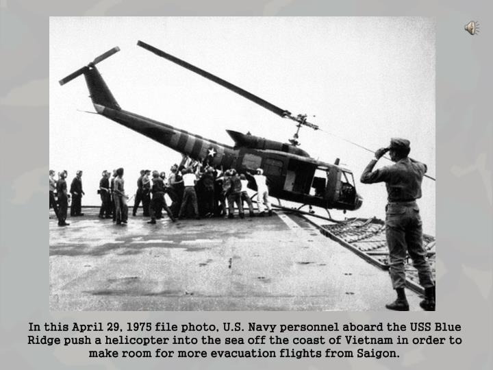 In this April 29, 1975 file photo, U.S. Navy personnel aboard the USS Blue Ridge push a helicopter into the sea off the coast of Vietnam in order to make room for more evacuation flights from Saigon.