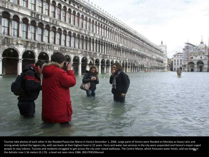 Tourists take photos of each other in the flooded Piazza San Marco in Venice December 1, 2008. Large parts of Venice were flooded on Monday as heavy rains and strong winds lashed the lagoon city, with sea levels at their highest level in 22 years. Ferry and water taxi services in the city were suspended and Venice's mayor urged people to stay indoors. Tourists and residents struggled to get across the city over raised walkways. The Centro Maree, which forecasts water levels, said sea levels in the Adriatic rose 1.56 meters (5.1 ft) - a level not seen since 1986. (REUTERS/Manuel