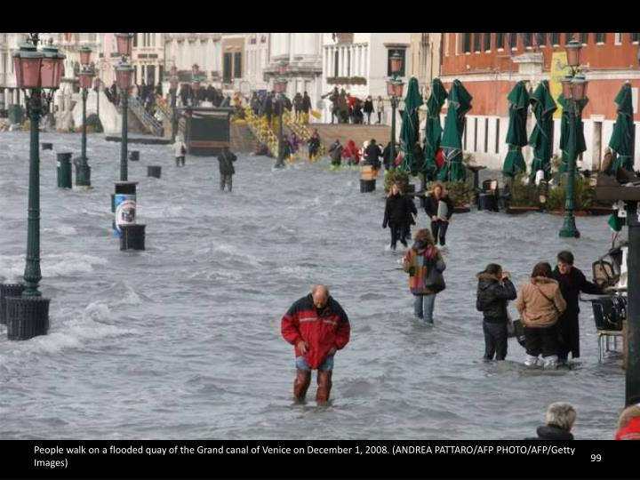 People walk on a flooded quay of the Grand canal of Venice on December 1, 2008. (ANDREA PATTARO/AFP PHOTO/AFP/Getty Images)