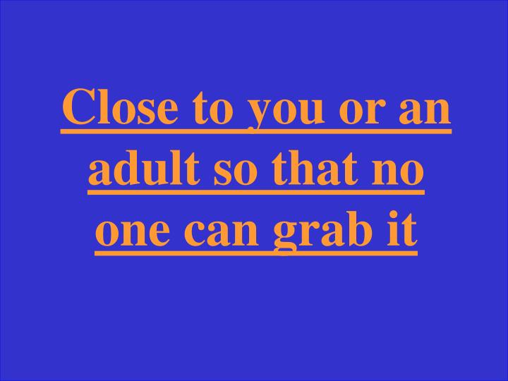 Close to you or an adult so that no one can grab it