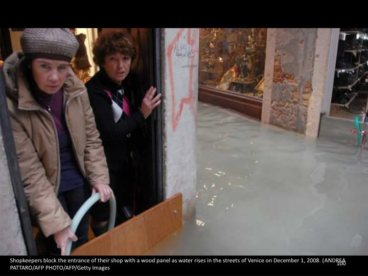 Shopkeepers block the entrance of their shop with a wood panel as water rises in the streets of Venice on December 1, 2008. (ANDREA PATTARO/AFP PHOTO/AFP/Getty Images