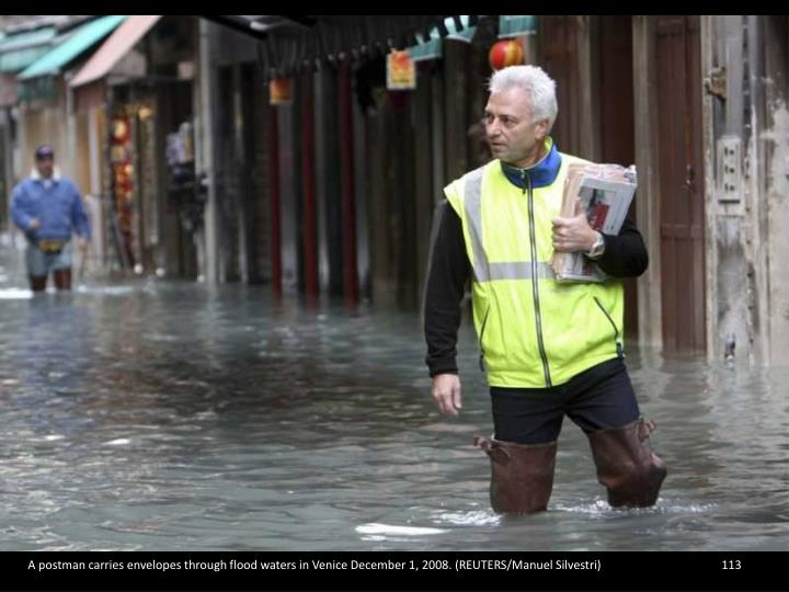 A postman carries envelopes through flood waters in Venice December 1, 2008. (REUTERS/Manuel Silvestri)