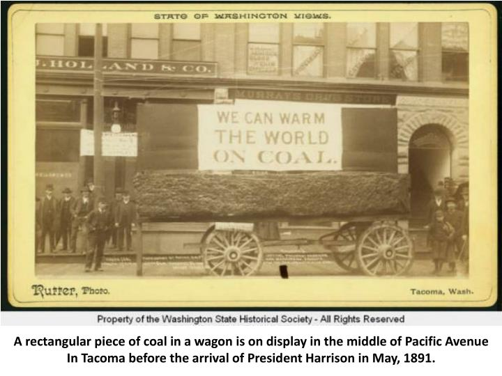 A rectangular piece of coal in a wagon is on display in the middle of Pacific Avenue