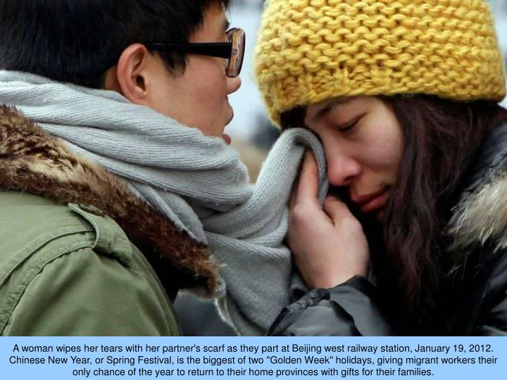 "A woman wipes her tears with her partner's scarf as they part at Beijing west railway station, January 19, 2012. Chinese New Year, or Spring Festival, is the biggest of two ""Golden Week"" holidays, giving migrant workers their only chance of the year to return to their home provinces with gifts for their families."