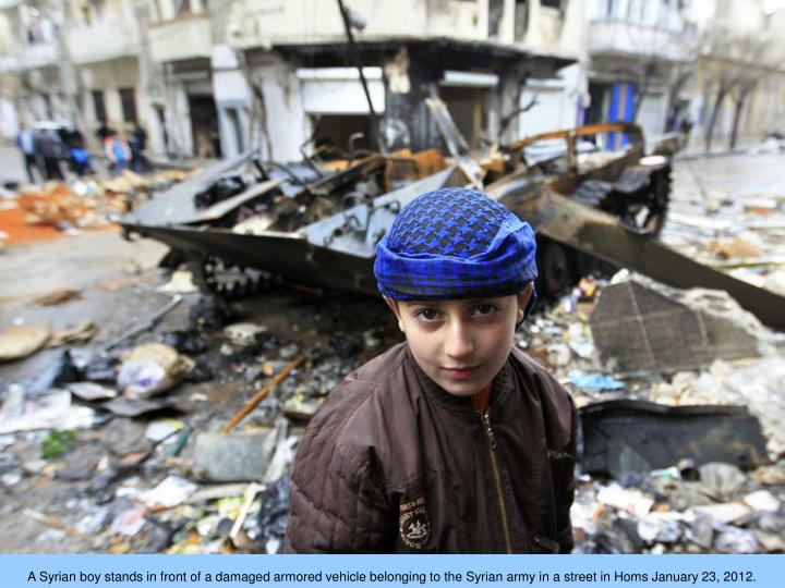A Syrian boy stands in front of a damaged armored vehicle belonging to the Syrian army in a street in Homs January 23, 2012.