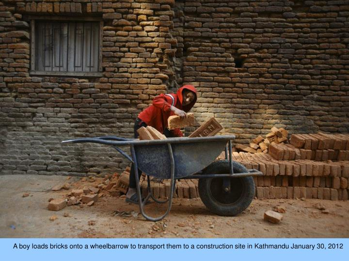 A boy loads bricks onto a wheelbarrow to transport them to a construction site in Kathmandu January 30, 2012