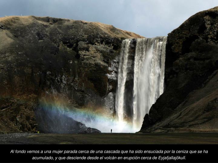 Al fondo vemos a una mujer parada cerca de una cascada que ha sido ensuciada por la ceniza que se ha acumulado, y que desciende desde el volcn en erupcin cerca de Eyjafjallajkull.