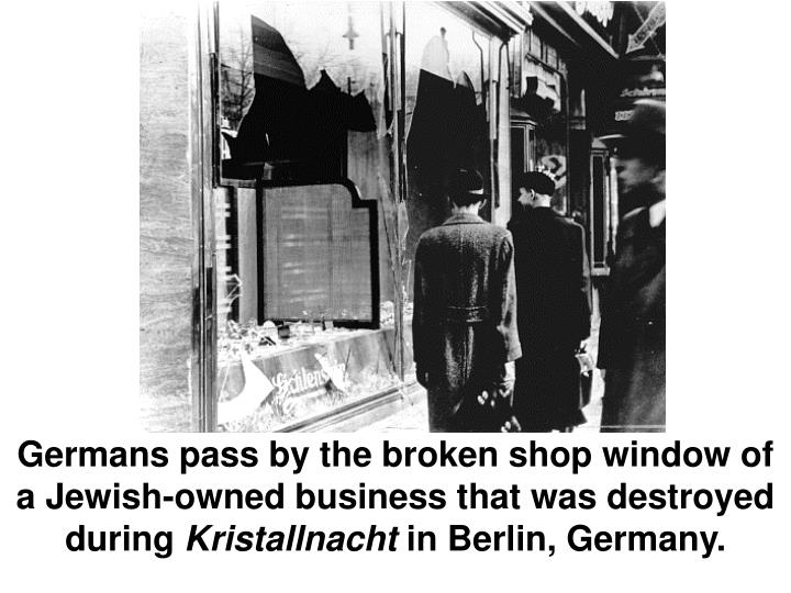 Germans pass by the broken shop window of a Jewish-owned business that was destroyed during
