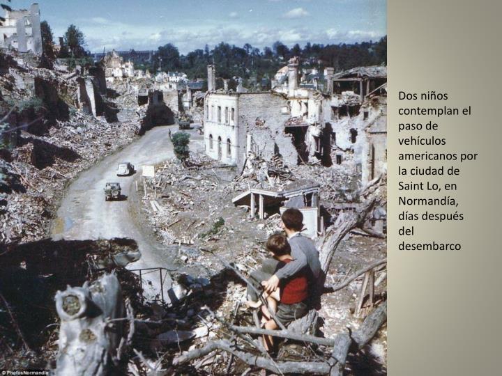 Dos niños contemplan el paso de vehículos americanos por la ciudad de Saint Lo, en Normandía, días después del desembarco
