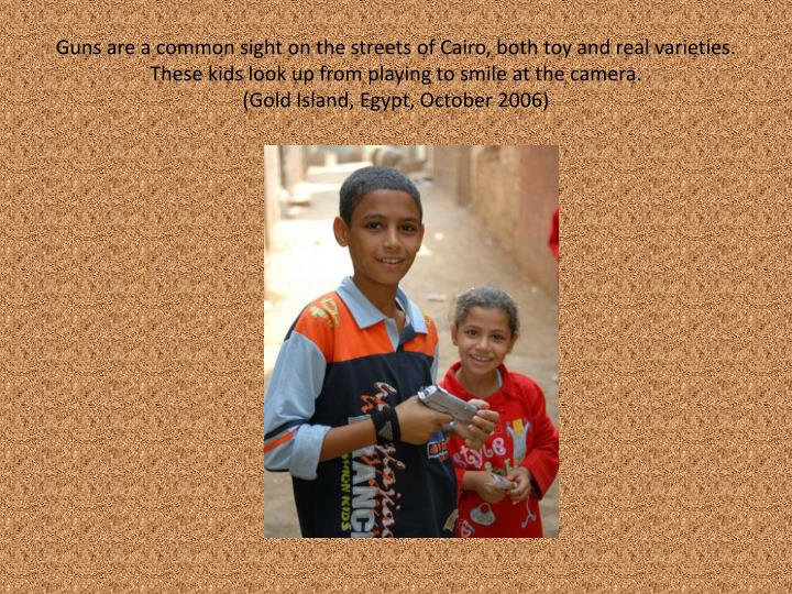 Guns are a common sight on the streets of Cairo, both toy and real varieties. These kids look up from playing to smile at the camera.