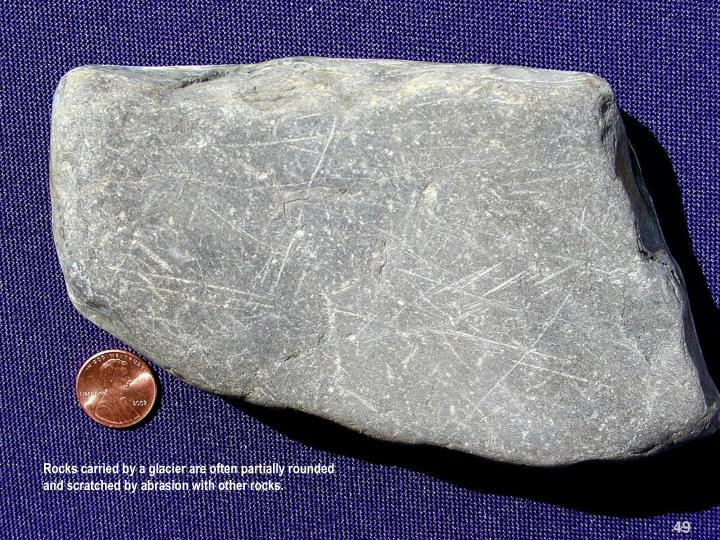 Rocks carried by a glacier are often partially rounded  and scratched by abrasion with other rocks.
