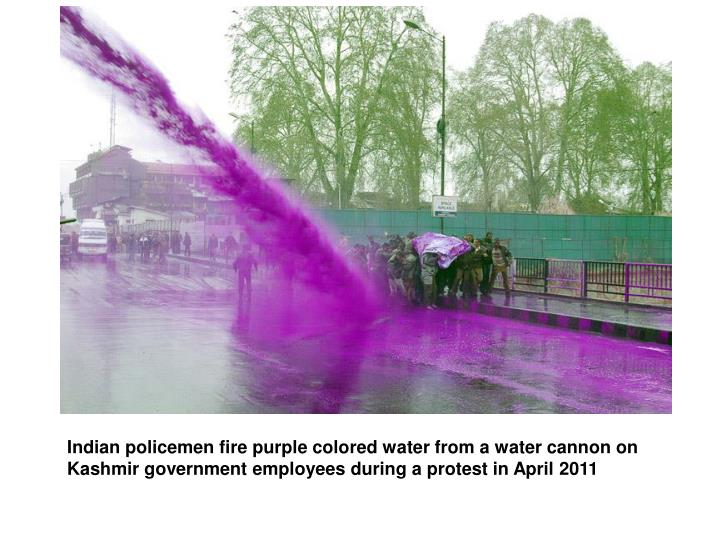 Indian policemen fire purple colored water from a water cannon on Kashmir government employees during a protest in April 2011