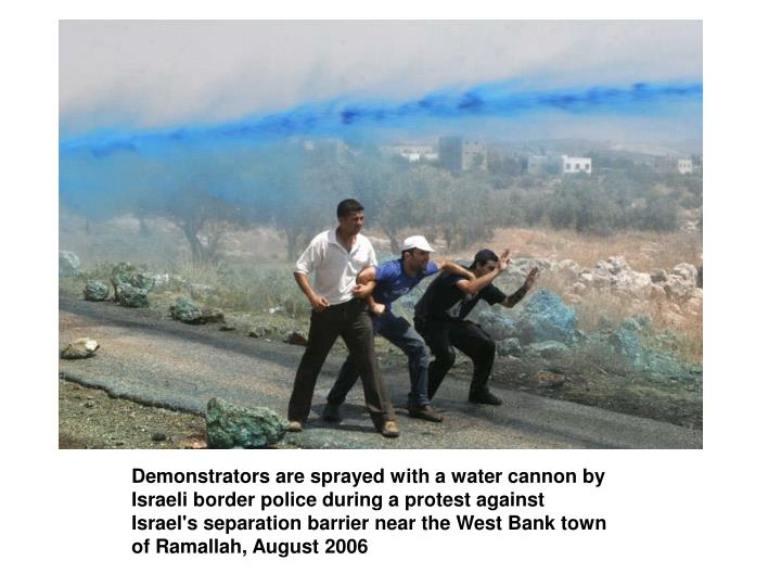 Demonstrators are sprayed with a water cannon by Israeli border police during a protest against Israel's separation barrier near the West Bank town of Ramallah, August 2006