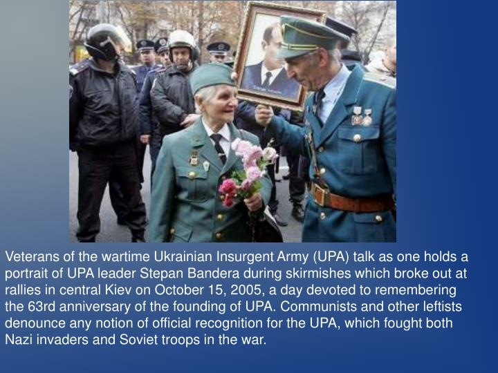 Veterans of the wartime Ukrainian Insurgent Army (UPA) talk as one holds a portrait of UPA leader Stepan Bandera during skirmishes which broke out at rallies in central Kiev on October 15, 2005, a day devoted to remembering the 63rd anniversary of the founding of UPA. Communists and other leftists denounce any notion of official recognition for the UPA, which fought both Nazi invaders and Soviet troops in the war.
