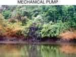 mechanical pump sprinkling oil across a creek and vegetation