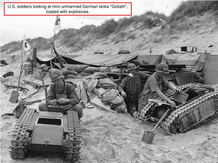 """U.S. soldiers looking at mini-unmanned German tanks """"Goliath"""", loaded with explosives."""