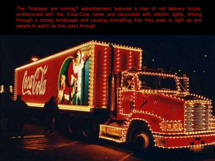 """The """"Holidays are coming!"""" advertisement features a train of red delivery trucks, emblazoned with the Coca-Cola name and decorated with electric lights, driving through a snowy landscape and causing everything that they pass to light up and people to watch as they pass through."""