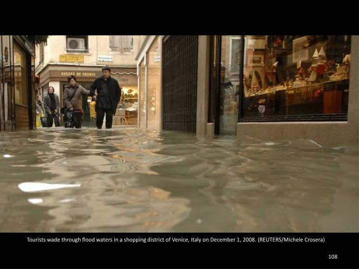 Tourists wade through flood waters in a shopping district of Venice, Italy on December 1, 2008. (REUTERS/Michele Crosera)