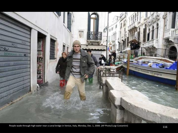 People wade through high water near a canal bridge in Venice, Italy, Monday, Dec. 1, 2008. (AP Photo/Luigi Costantini)