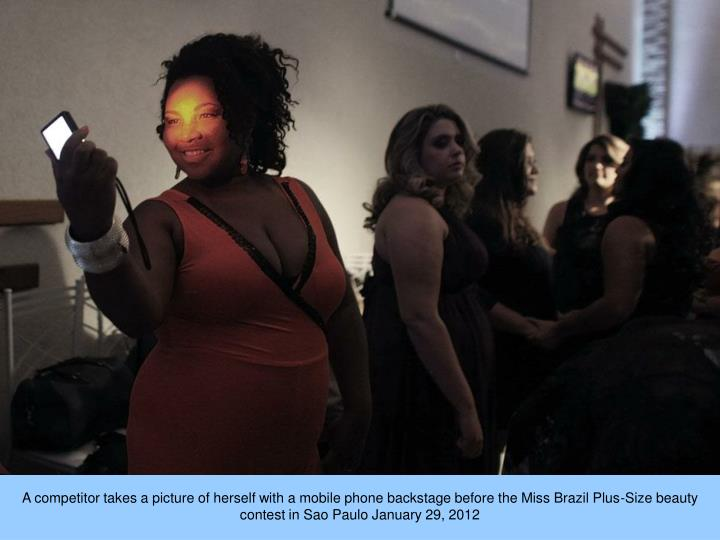 A competitor takes a picture of herself with a mobile phone backstage before the Miss Brazil Plus-Size beauty contest in Sao Paulo January 29, 2012