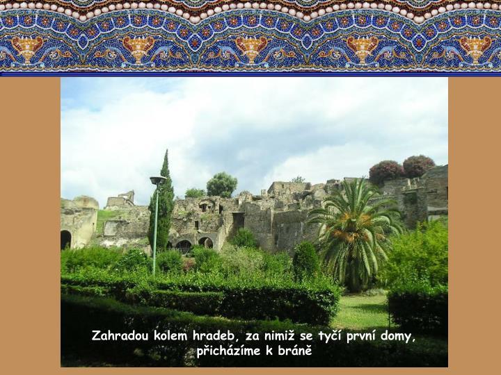 Zahradou kolem hradeb, za nimiž se tyčí první domy, přicházíme k bráně